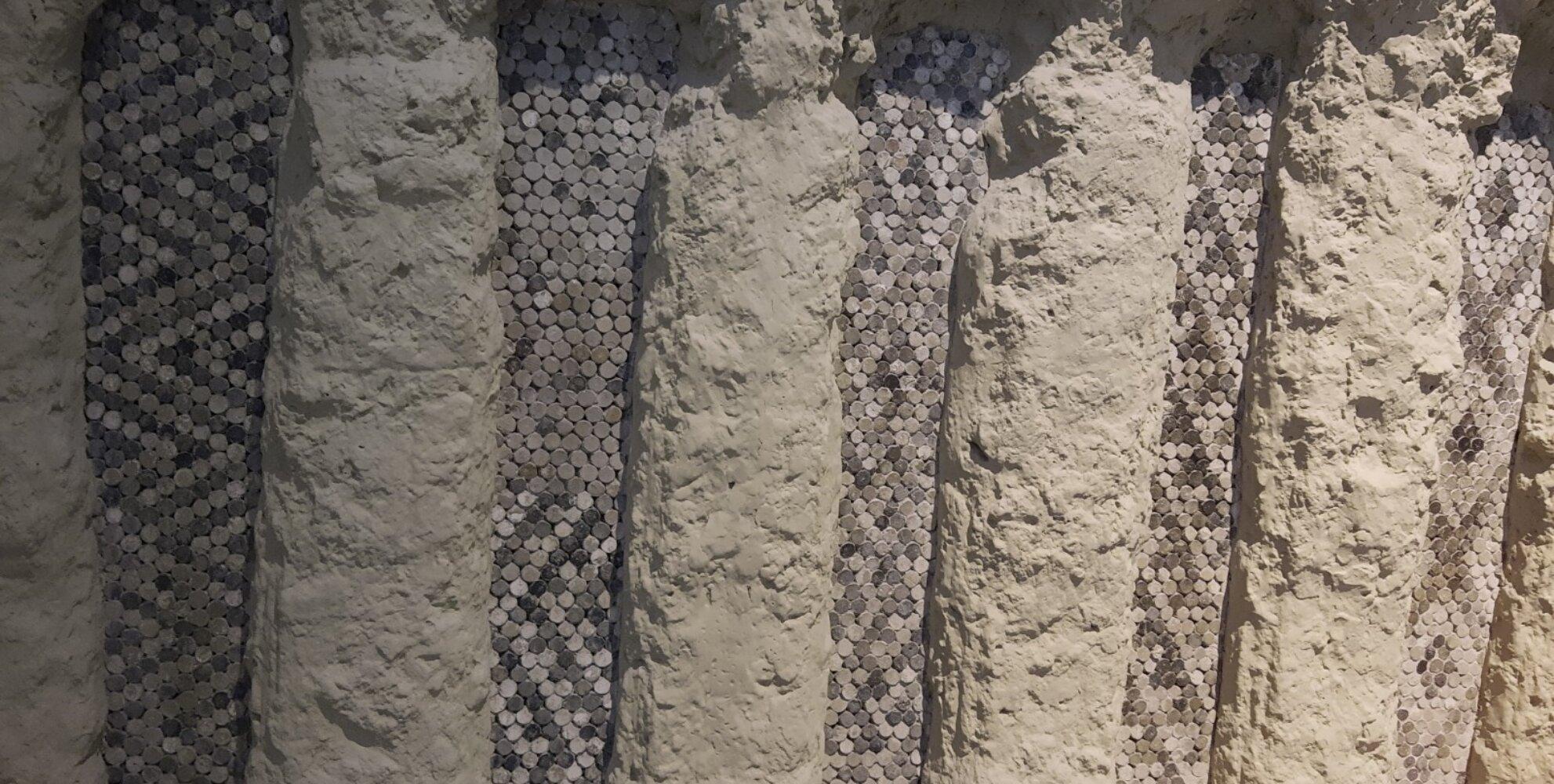Stiftmosaikfassaden der Tempelanlage Inanna Uruk/Warka [Irak] aus der 2. Hälfte des 4. Jahrhunderts v. Chr.  Zu sehen ist ein Teil der Stiftmosaikfassade, die angeschlossen war an einen Empfangspalast.  Der zur kultischen Verehrung der Göttin Inanna diente. Die lehmverputzten Mauern wurden mit 10 cm Langen Tonstiften mit schwarz, rot und weißen Körpern zu geometrischen Mustern eingedrückt.